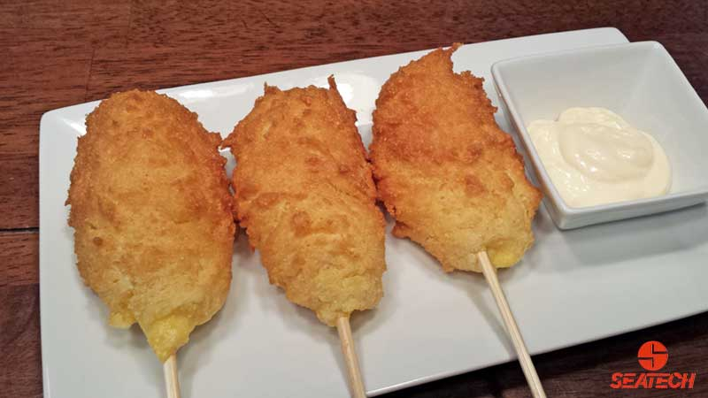 A photograph of Argentine red shrimp corn dogs with a lemon garlic aioli.