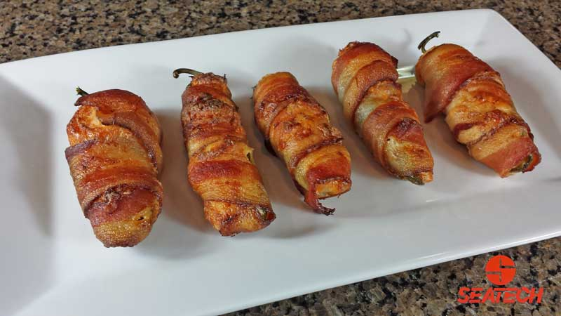plate with bacon wrapped crab stuffed jalapeno poppers.