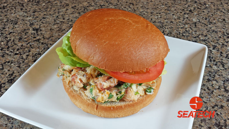 A photograph of a Chilean crab meat burger with lettuce and tomato.