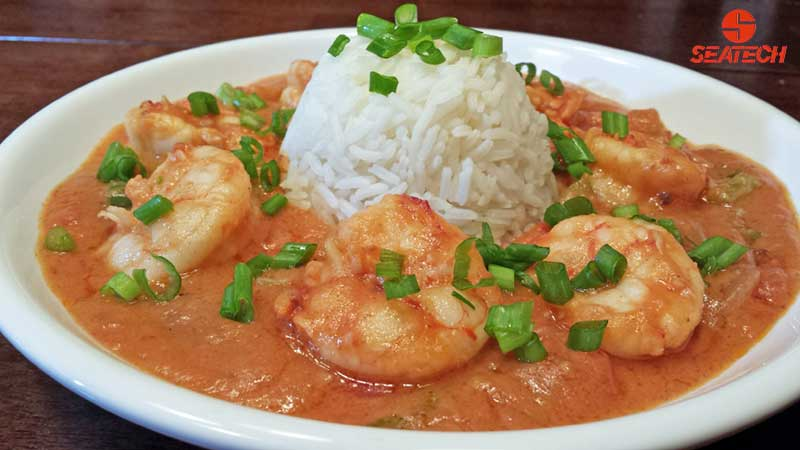 A photograph of Argentine red shrimp gumbo etouffee with steamed rice and sliced scallions.